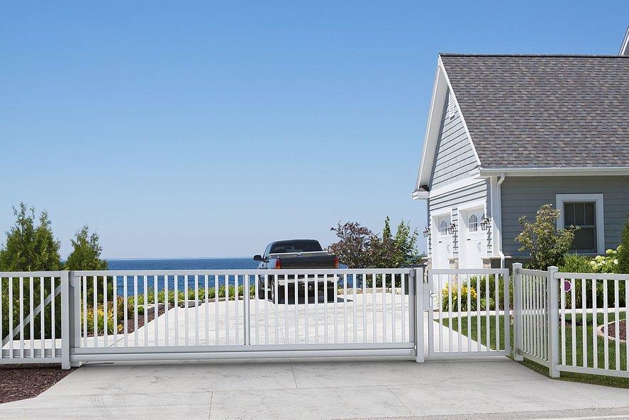 grand portail coulissant de couleur blanche avec clôture à barres à l'entrée d'une maison sur les falaises