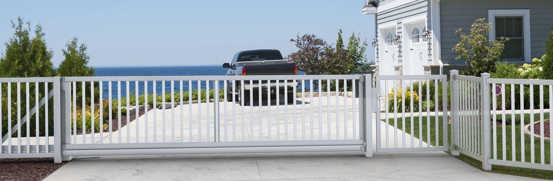 clôture à barres blanche avec portail coulissant et portillon de jardin devant une maison au bord de la mer