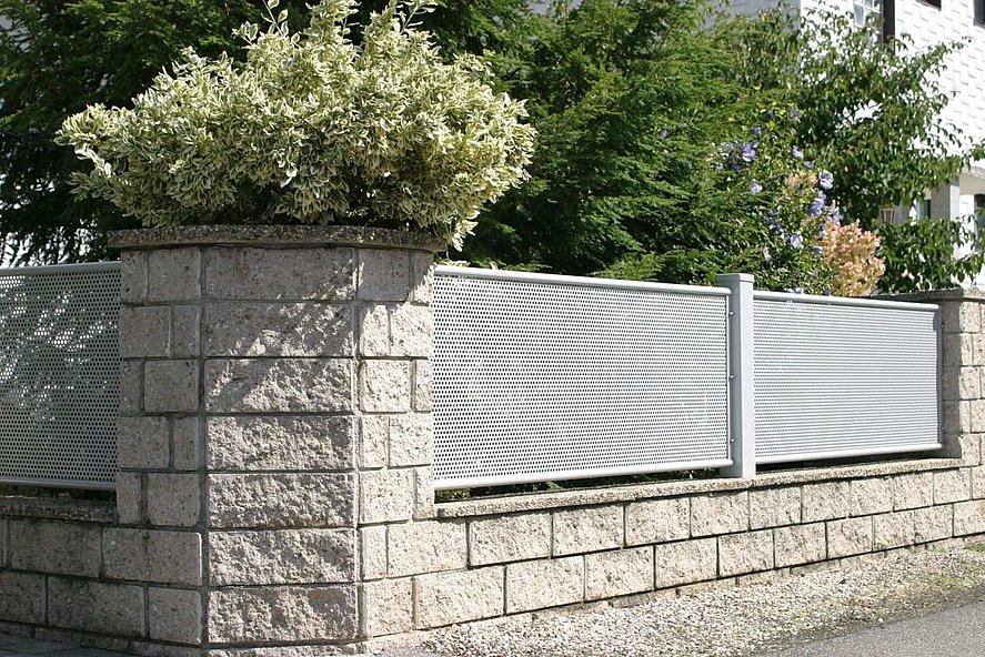 Clôture de jardin blanche en tôle perforée sur socles muraux avec briques et plantes