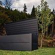 Coffre de rangement couleur anthracite dans un jardin avec cabane en pierre