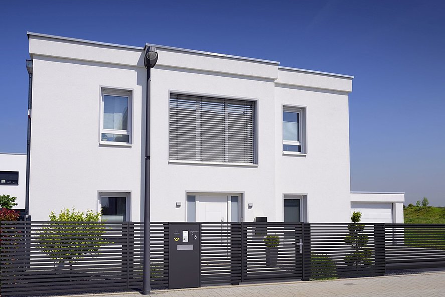 Colonne-boîte aux lettres intégrée à la clôture à lattes moderne MAGNUS devant une maison unifamiliale moderne à deux niveaux