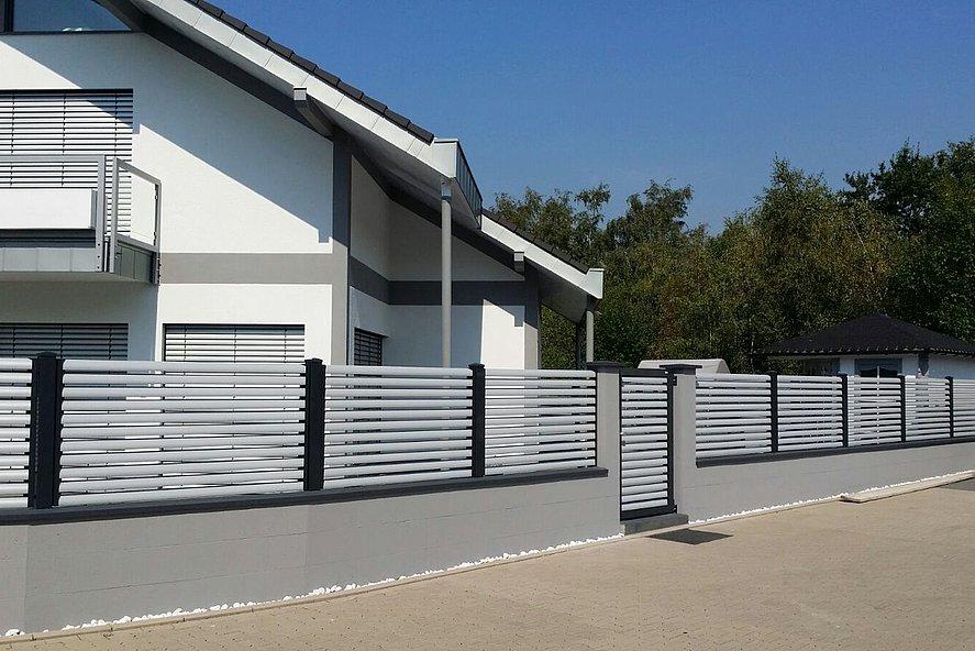 Clôture à lamelles bicolore, lamelles blanches et poteaux gris foncé avec portillon de jardin devant une maison unifamiliale en France