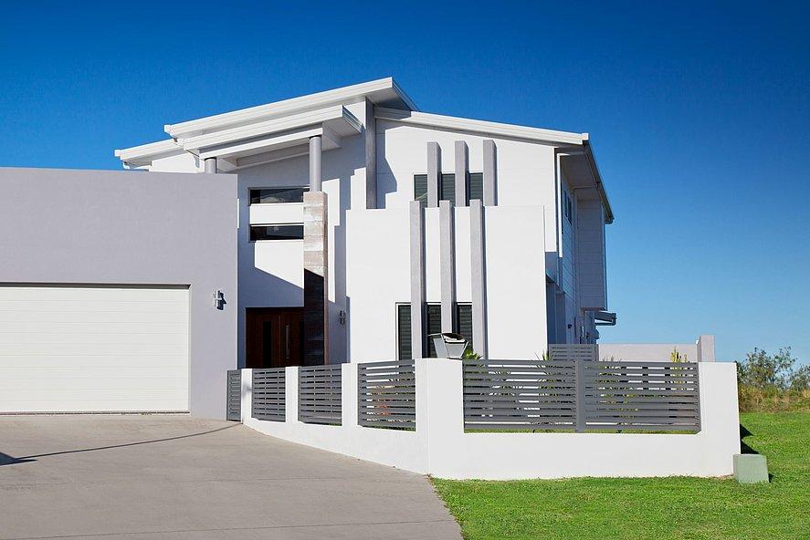 clôture à lamelles moderne grise sur un mur blanc devant une jolie villa avec jardin