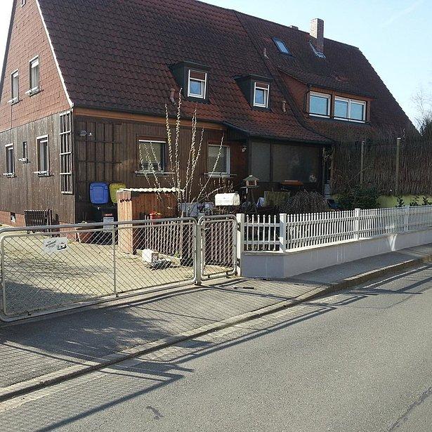 clôture à palissade blanche avec portail d'entrée après la rénovation de la clôture