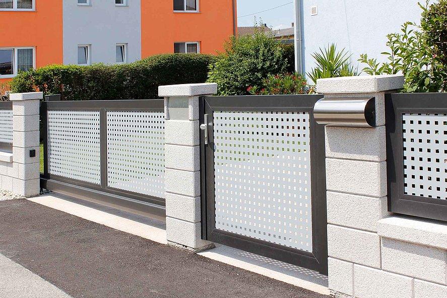 Portail coulissant et portillon de jardin sur clôture bicolore en tôle perforée avec socles muraux en briques
