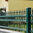 Vue rapprochée d'une clôture à barres couleur vert mousse en aluminium finition ferronnerie d'art avec ornements