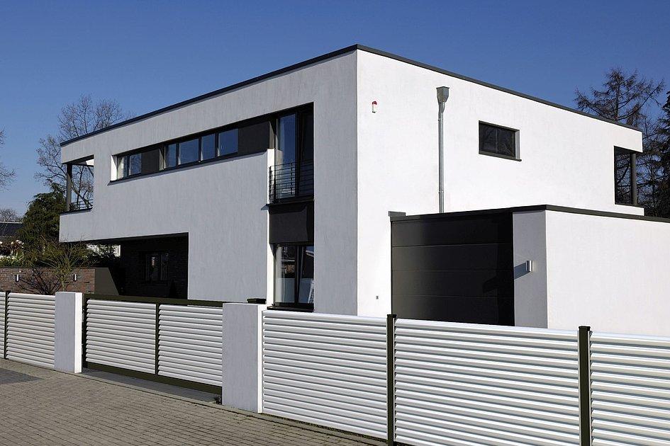 clôture à lamelles moderne avec portail d'entrée blanc devant une villa moderne