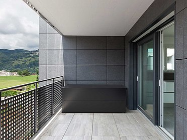 Coffre de rangement anthracite sur un balcon moderne avec balustrade en tôle perforée