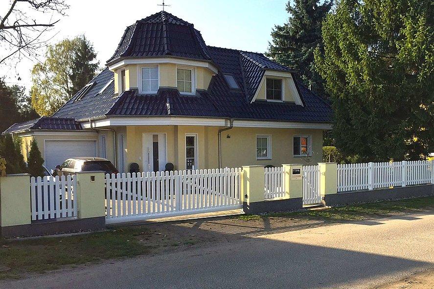 clôture à lattes blanche avec portail d'entrée devant une villa avec jardin et toit en bardeau