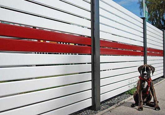 [Translate to Fransösich:] Moderner Sichtschutzzaun aus Aluminium mit Querlatten in weiß und rot, davor sitzt ein Hund