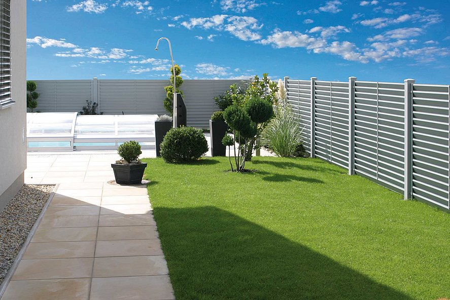 Clôture occultante en aluminium avec lamelles blanches entourant un jardin moderne