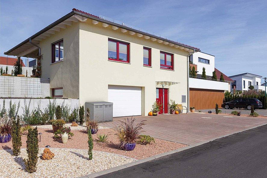 Abri poubelles moderne en aluminium couleur argent à l'entrée d'une maison avec jardin de rocaille