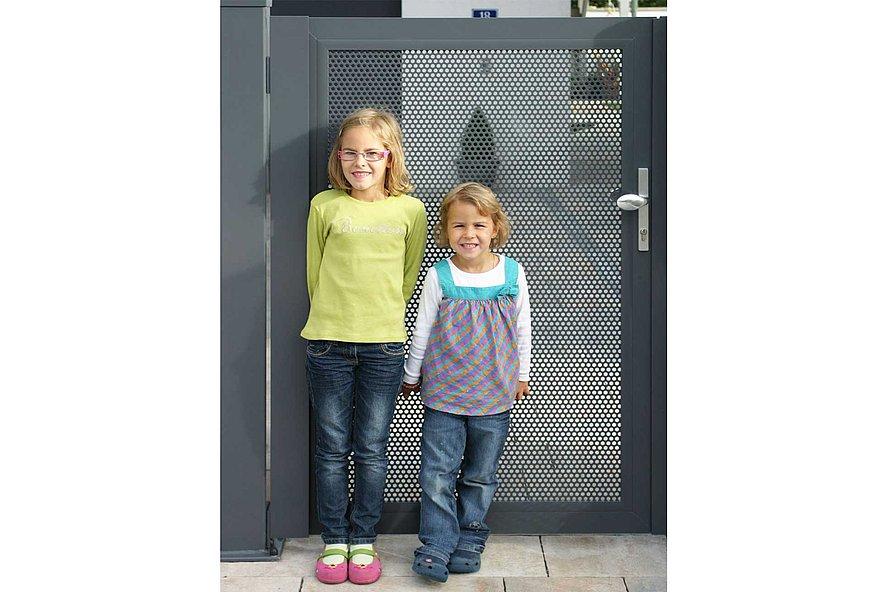 deux jeunes filles se tenant sur un portillon en tôle perforée à l'entrée de la maison