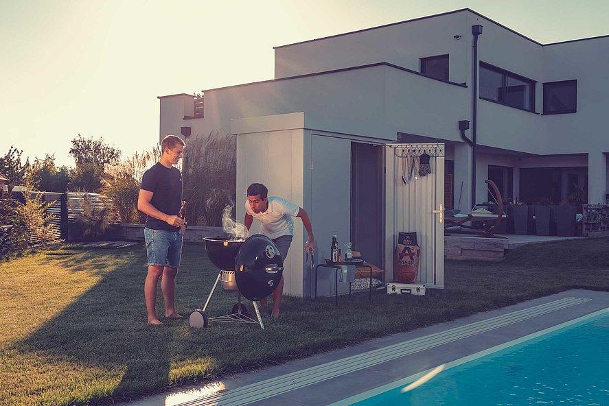 [Translate to Fransösich:] Gartenhütte aus Stahl in silber metallic steht im Hintergrund, davor grillen zwei Freunde