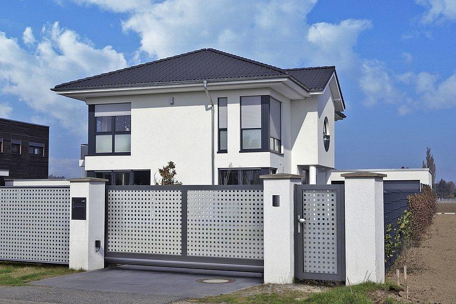 portail coulissant élégant et portillon de jardin bicolore en gris et gris foncé devant une maison individuelle