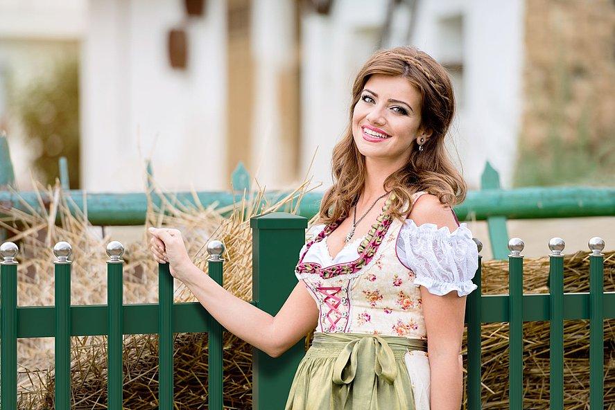jeune femme en dirndl se tenant devant une clôture à palissade verte avec embouts ronds argentés