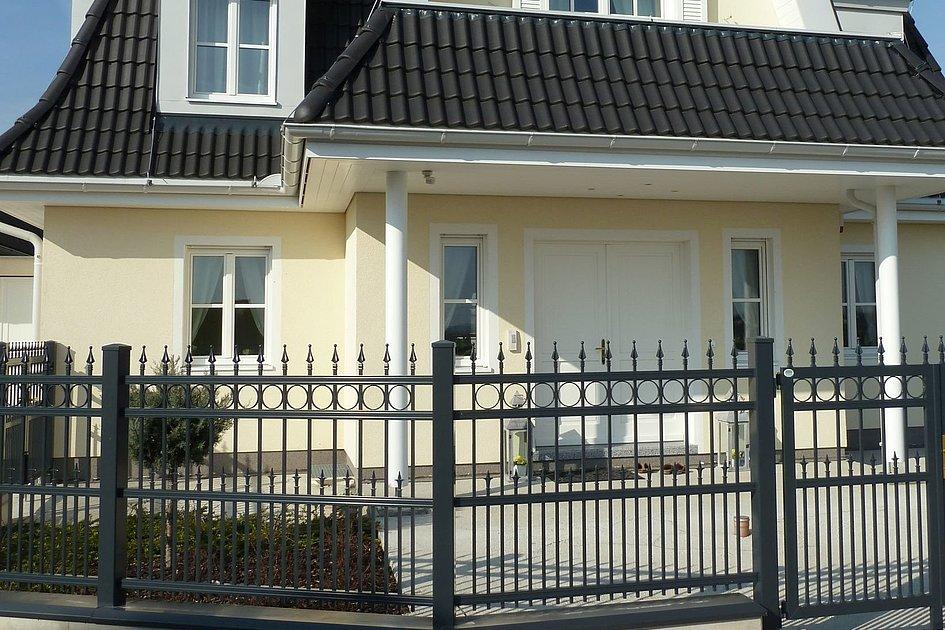 Clôture en aluminium finition ferronnerie d'art, devant une maison avec des colonnes d'entrée