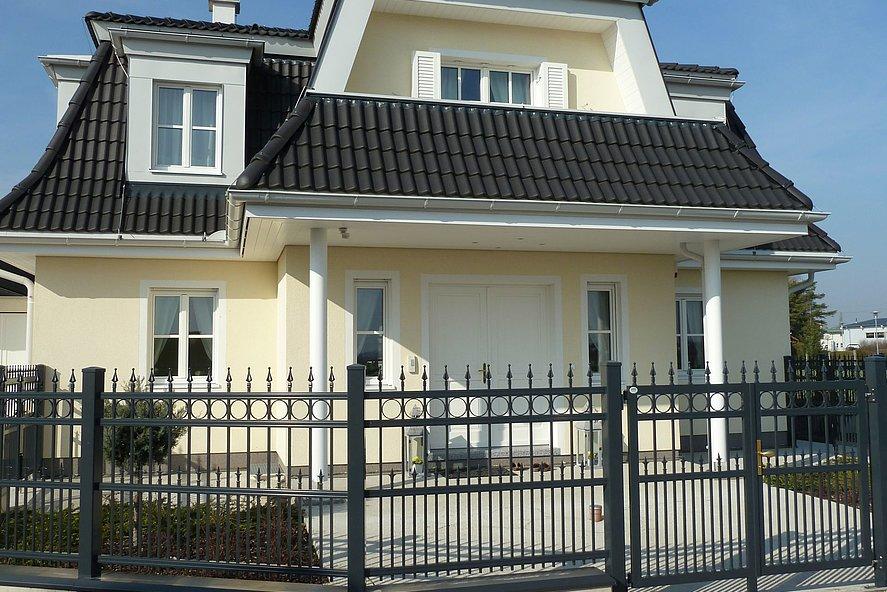 Clôture à barres en aluminium couleur anthracite avec ornements tels que la finition ferronnerie d'art devant une maison de style colonial