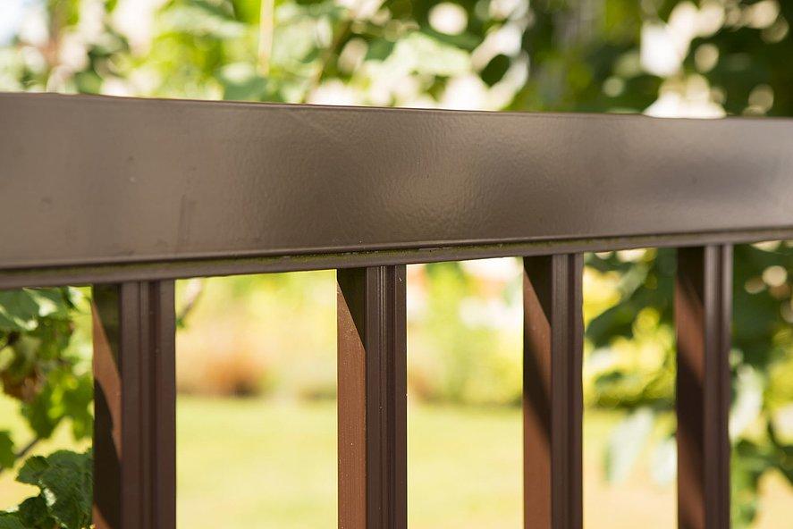 Vue rapprochée d'un élément de clôture à barres couleur marron chocolat