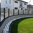 Vue intérieure d'une clôture à lamelles blanche entourant une propriété incurvée avec pelouse et pierres blanches