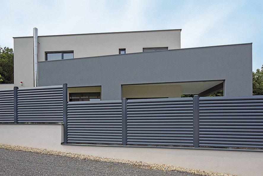Clôture à lamelles occultantes couleur grise devant une maison à architecture moderne