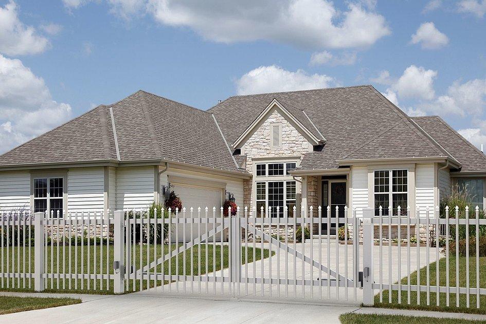 Portail à double battant avec palissades à plusieurs couleurs devant une villa familiale classique