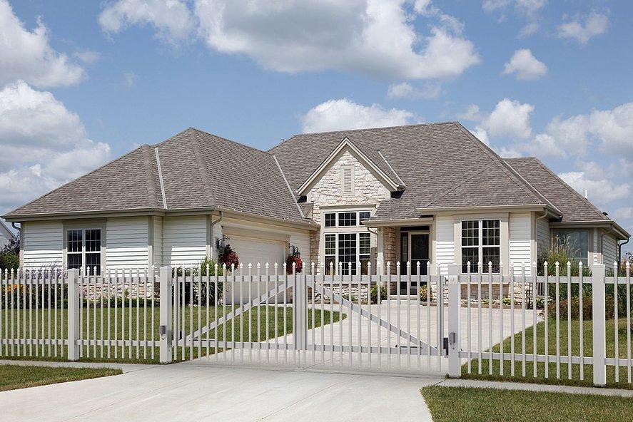 Portail à double battant pour clôture à palissade avec barres rondes couleur gris clair et embouts ronds de couleur blanche, devant une maison avec murs en pierre