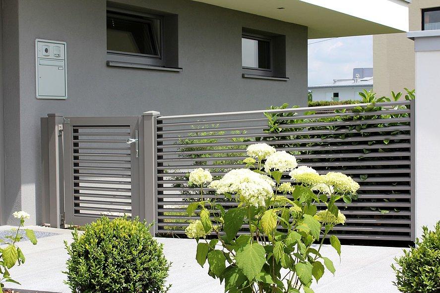 Portillon de jardin avec élément de clôture à lamelles en aluminium couleur gris noble avec des buissons devant