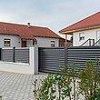 Clôture grise avec lamelles occultantes, portail de jardin et portillon de jardin autour d'une maison moderne
