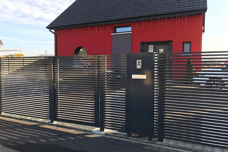 Colonne-boîte aux lettres sur clôture moderne, toutes deux de couleur anthracite, devant une maison individuelle à façade rouge