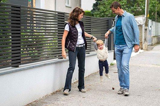 [Translate to Fransösich:] Moderner Aluminiumzaun mit Querlatten aus Aluminium auf einer Steinmauer, davor spaziert eine Familie