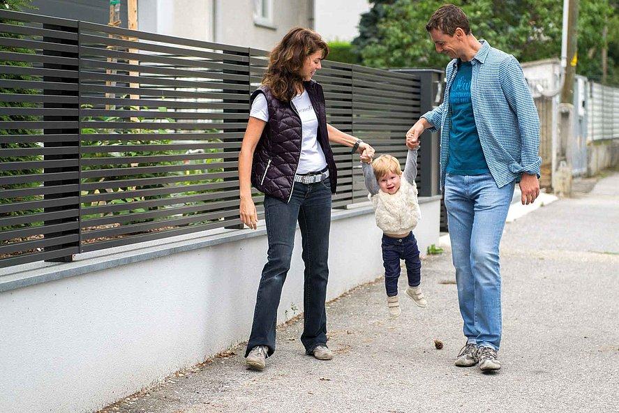 clôture à lattes moderne couleur anthracite sur socle mural blanc devant laquelle se tient une jeune famille moderne