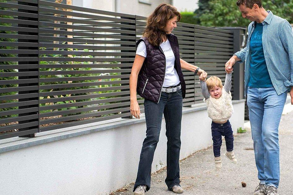 Famille avec enfant devant une clôture de jardin moderne à lattes horizontales, couleur anthracite