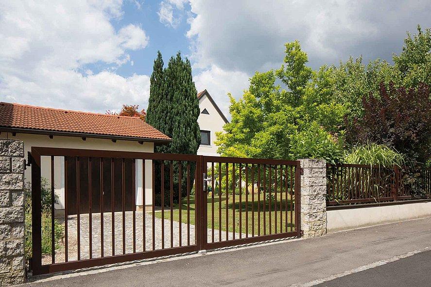Portail à double battant sur clôture à barres marron devant une grande propriété