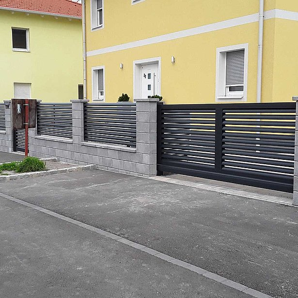 nouvelle clôture à lattes en aluminium de couleur noire devant une maison jaune