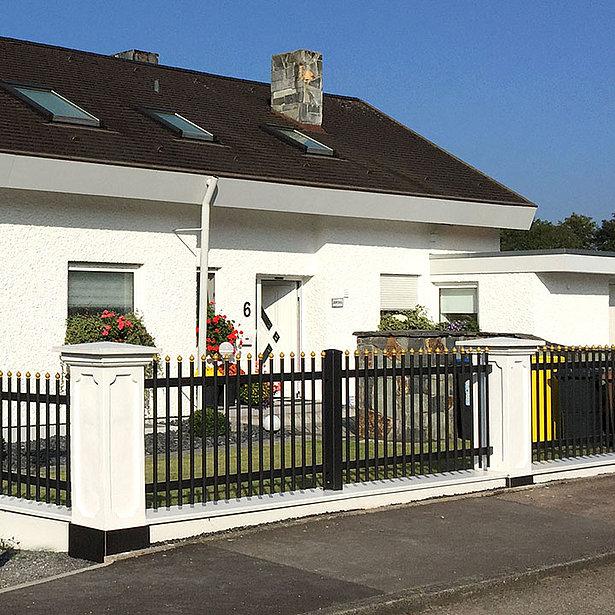 Clôture à palissade avec barres rondes noires et caches dorés coupe oignon entourant une maison unifamiliale classique