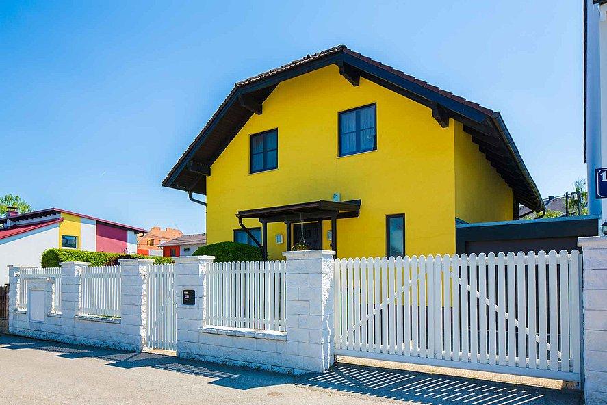 Portail à double battant et portail de jardin avec lattes en aluminium servant de portail d'entrée à une grande maison jaune