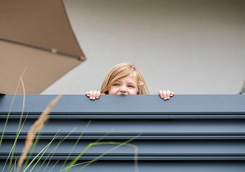 [Translate to Fransösich:] Kind schaut über einen Aluminiumzaun mit Querlatten in anthrazit