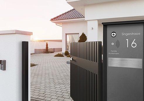Colonne-boîte aux lettres grise ouverte près d'un portillon de jardin à lattes moderne en aluminium, à l'entrée d'une villa