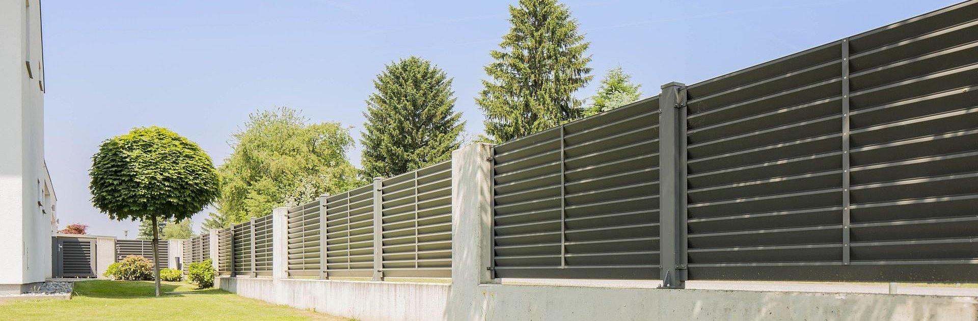 clôture en aluminium moderne avec lattes transversales grises servant de limite de jardin