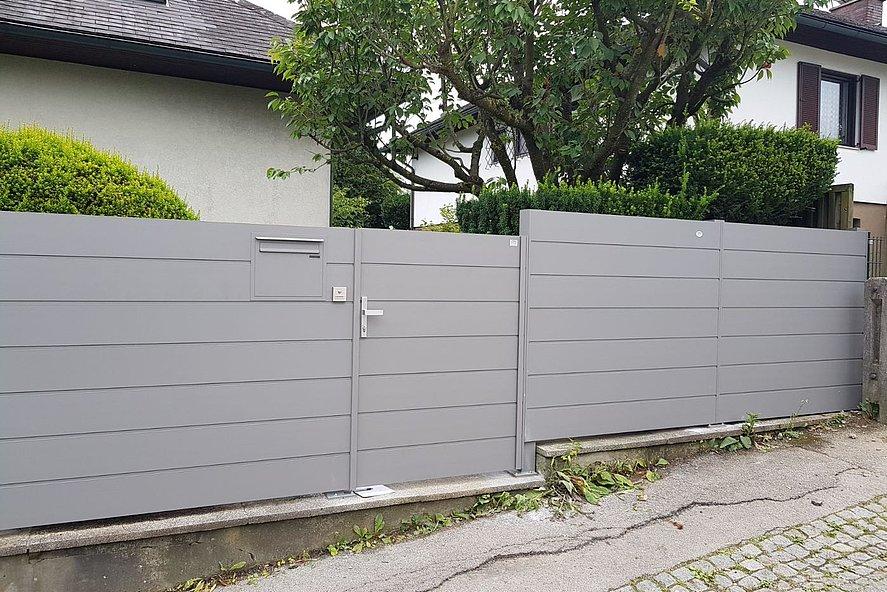 clôture occultante moderne avec portillon de jardin couleur aluminium blanc délimitant le jardin d'une maison unifamiliale
