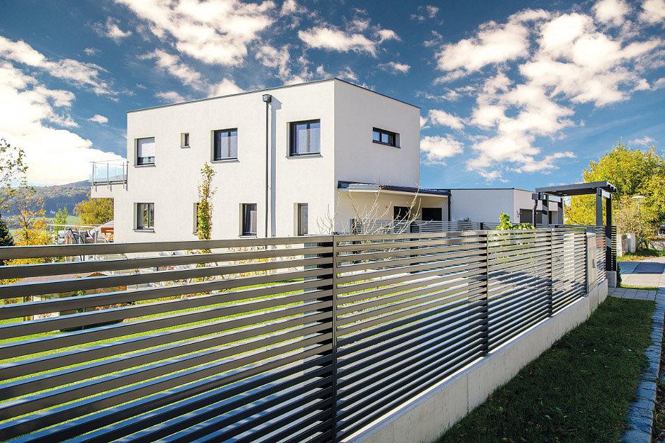 Clôture de jardin grise avec lattes horizontales devant une maison moderne