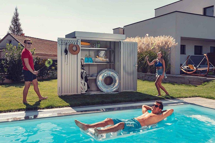 [Translate to Fransösich:] Gartenhütte in silber metallic gefüllt mit diversen Gartenutensilien geöffnet neben einem Pool