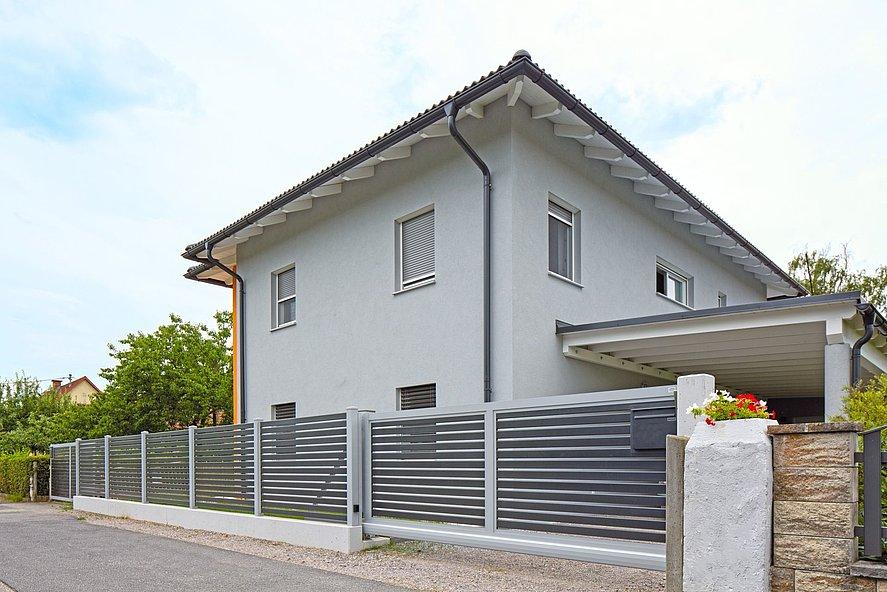Clôture en aluminium et portail coulissant avec lattes transversales au design moderne devant une maison unifamiliale des années 2000
