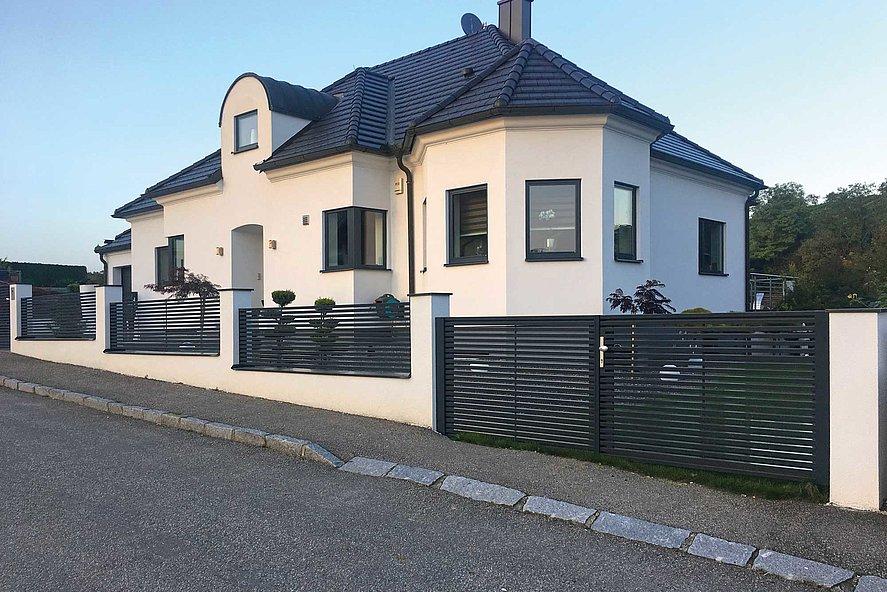 Clôture à lattes avec lattes transversales et portail à double battant devant une grande maison unifamiliale sur une pente