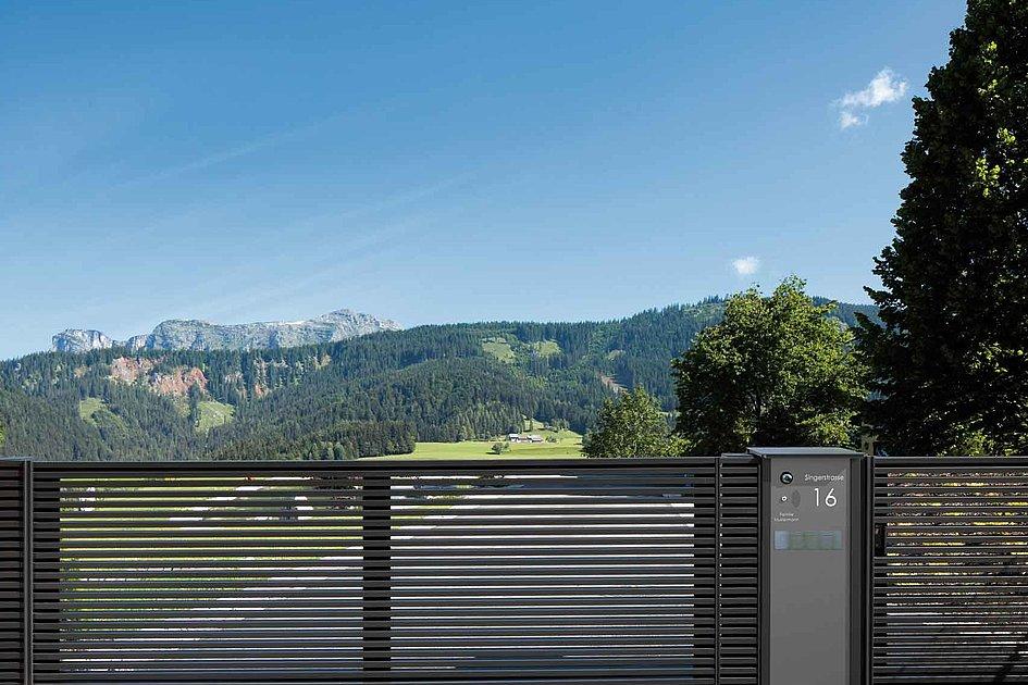 portail de jardin moderne en aluminium à lattes transversales fines devant une maison cubique moderne dans les montagnes