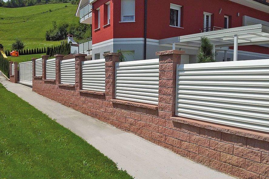 Clôture de jardin blanche avec lamelles sur socle mural en briques entourant une maison d'appartement dans les montagnes