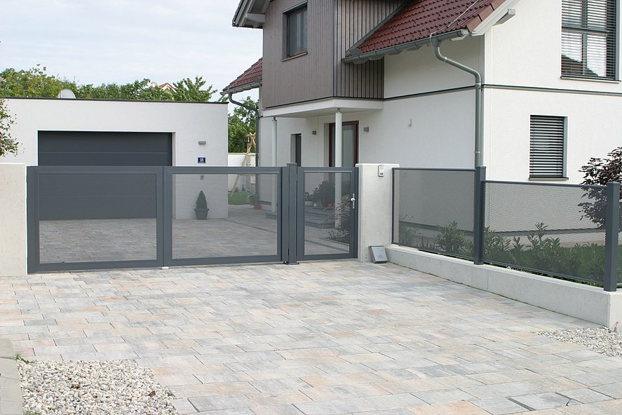 portail électrique à double battant et clôture de jardin en tôle perforée couleur grise devant une grande maison unifamiliale avec garage