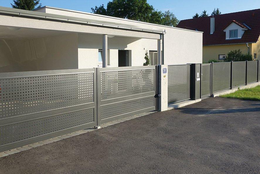 Portail à double battant avec portillon de jardin et clôture de jardin en tôle perforée grise élégante devant une maison à architecture moderne