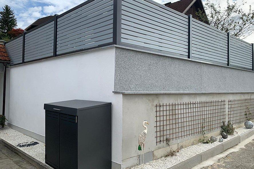 [Translate to Fransösich:] Mülltonnenbox für zwei Tonnen in anthrazit und Gartenzaun Modell TESLA aus Aluminium in grau im Hintergrund